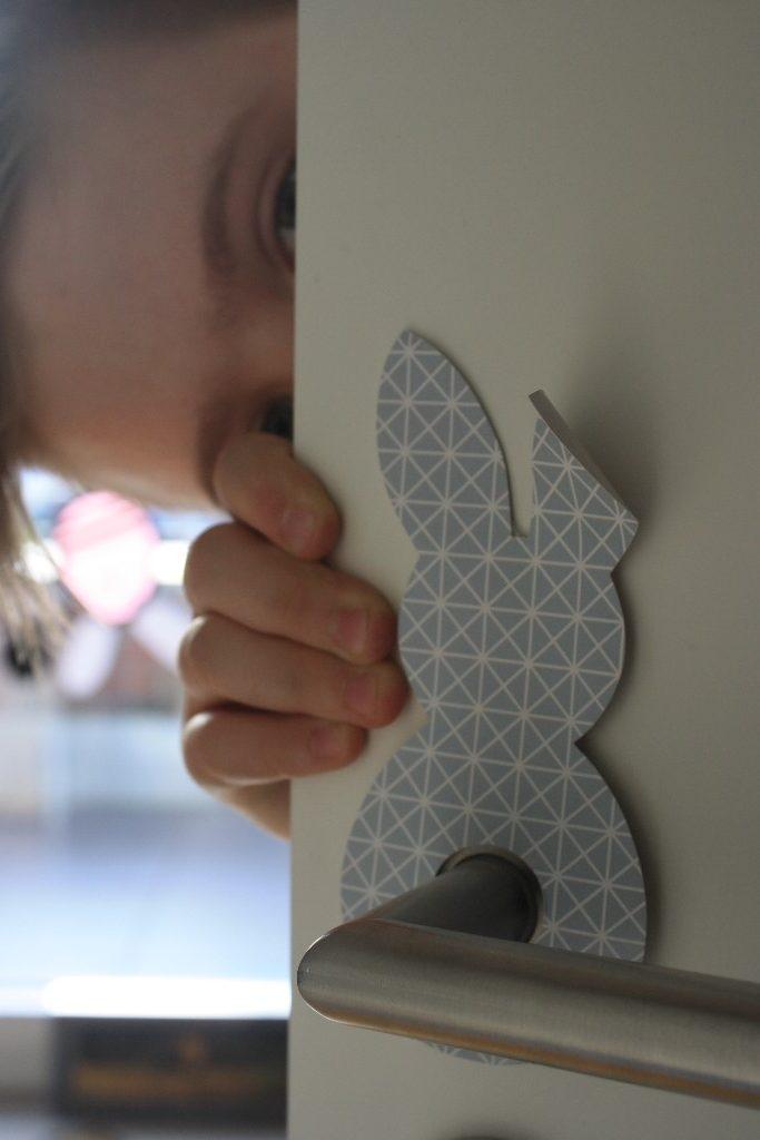 Osterhasenspion am Türgriff mit Lausebub, der um die Tür schaut
